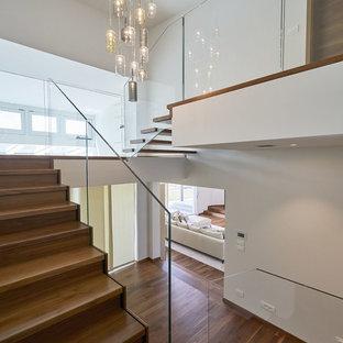 Mittelgroße Moderne Treppe in U-Form mit gebeizten Holz-Treppenstufen, gebeizten Holz-Setzstufen und Glasgeländer in München