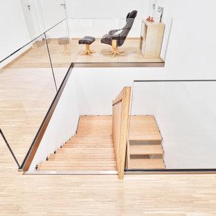 На фото: п-образная лестница среднего размера в стиле модернизм с деревянными ступенями, деревянными перилами и обоями на стенах с
