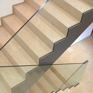 他の地域の大きいライムストーンのコンテンポラリースタイルのおしゃれなサーキュラー階段 (ライムストーンの蹴込み板、ガラスの手すり) の写真