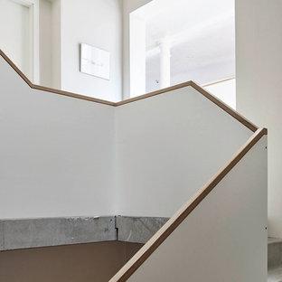 Diseño de escalera curva, industrial, extra grande, con escalones de hormigón y contrahuellas de hormigón