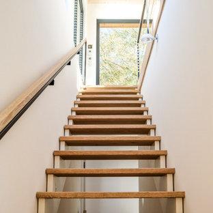 Imagen de escalera recta y papel pintado, de tamaño medio, sin contrahuella, con escalones de madera, barandilla de cable y papel pintado