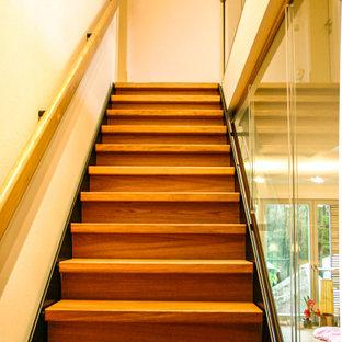 Ejemplo de escalera recta y papel pintado, de tamaño medio, con escalones de madera, contrahuellas de madera, barandilla de vidrio y papel pintado