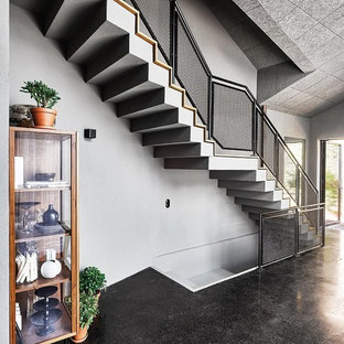Staircase - mid-sized industrial painted straight metal railing staircase idea in Cologne with painted risers