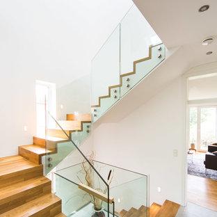 Mittelgroße Moderne Holztreppe in L-Form mit Holz-Setzstufen und Glasgeländer in Frankfurt am Main