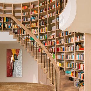 Immagine di una grande scala curva classica con pedata in legno, alzata in legno e parapetto in materiali misti