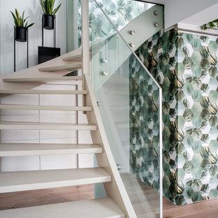 Modelo de escalera curva y papel pintado, actual, de tamaño medio, con escalones de madera, barandilla de vidrio y papel pintado