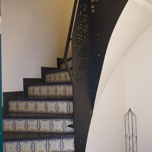 Foto di una piccola scala curva contemporanea con pedata piastrellata, alzata piastrellata e parapetto in metallo
