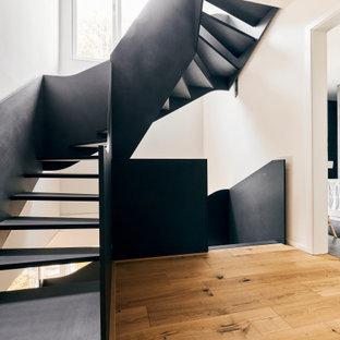 Foto på en mellanstor industriell svängd trappa i trä, med räcke i trä