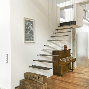Modelo de escalera suspendida, contemporánea, grande, sin contrahuella, con barandilla de cable y escalones de metal