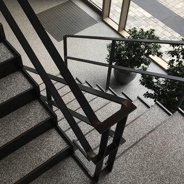 Stahltreppe zum Foyer. Belag: Natursteinteppich