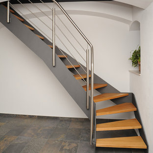 Inspiration for a small industrial painted curved open and metal railing staircase remodel in Other