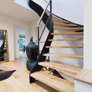 Foto på en mellanstor funkis l-trappa i trä, med räcke i flera material och öppna sättsteg