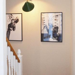 Ejemplo de escalera curva y papel pintado, clásica, pequeña, con escalones de madera, barandilla de madera y papel pintado