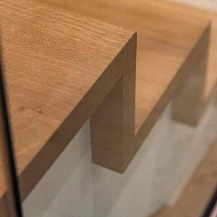 Exemple d'un escalier courbe tendance de taille moyenne avec des marches en bois, des contremarches en bois, un garde-corps en verre et un mur en parement de brique.