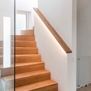Cette photo montre un escalier courbe tendance de taille moyenne avec des marches en bois, des contremarches en bois, un garde-corps en verre et un mur en parement de brique.