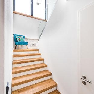 Aménagement d'un petit escalier scandinave en U avec des marches en bois et un garde-corps en verre.