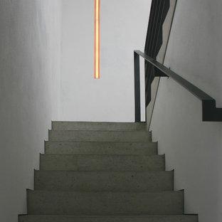 ハノーファーの巨大なコンクリートのコンテンポラリースタイルのおしゃれなかね折れ階段 (コンクリートの蹴込み板、金属の手すり) の写真