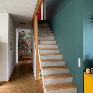 Imagen de escalera recta y papel pintado, actual, con escalones de madera, contrahuellas de hormigón, barandilla de madera y papel pintado