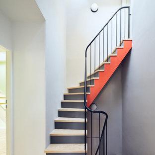 Gewendelte, Mittelgroße Moderne Holztreppe mit Holz-Setzstufen und Stahlgeländer in Berlin