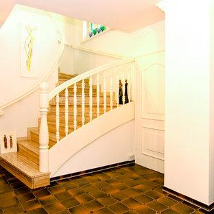 Ejemplo de escalera en U, tropical, con escalones con baldosas y contrahuellas con baldosas y/o azulejos