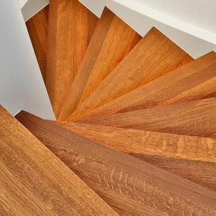 Diseño de escalera curva, contemporánea, pequeña, con escalones de madera, contrahuellas de madera y barandilla de madera