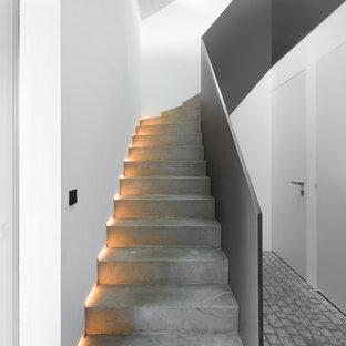 Imagen de escalera en L, minimalista, de tamaño medio, con escalones de hormigón y contrahuellas de hormigón