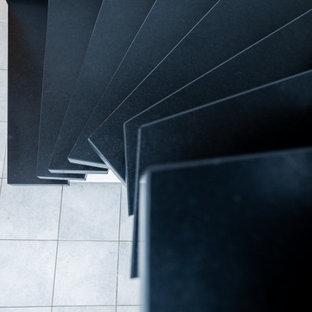 ケルンの巨大な大理石のコンテンポラリースタイルのおしゃれなサーキュラー階段 (大理石の蹴込み板、金属の手すり) の写真