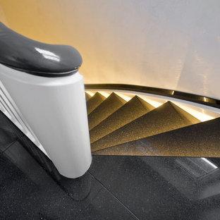 ケルンの中サイズの大理石のコンテンポラリースタイルのおしゃれなサーキュラー階段 (大理石の蹴込み板、木材の手すり) の写真