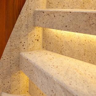Inredning av en lantlig liten svängd trappa i marmor, med sättsteg i marmor och räcke i trä