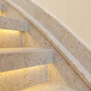 Diseño de escalera curva, de estilo de casa de campo, pequeña, con escalones de mármol, contrahuellas de mármol y barandilla de madera