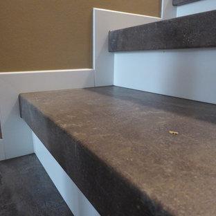 Modelo de escalera en L, actual, grande, con escalones de pizarra, contrahuellas de vidrio y barandilla de madera
