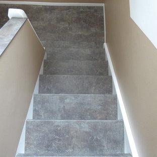フランクフルトの中サイズのスレートのミッドセンチュリースタイルのおしゃれな折り返し階段 (スレートの蹴込み板、混合材の手すり) の写真