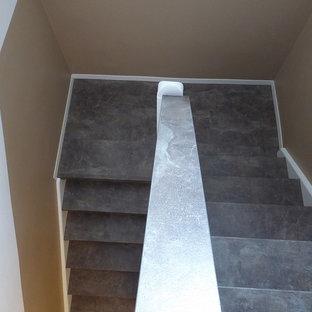 Imagen de escalera en U, contemporánea, extra grande, con escalones de pizarra, contrahuellas de metal y barandilla de metal