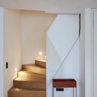 ケルンのフローリングのモダンスタイルのおしゃれな階段 (フローリングの蹴込み板、金属の手すり) の写真