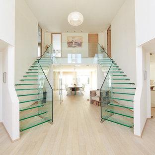 Ispirazione per una scala sospesa design di medie dimensioni con pedata in vetro e nessuna alzata
