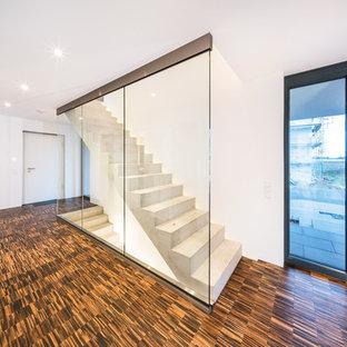 Modelo de escalera recta, moderna, de tamaño medio, con escalones de hormigón, contrahuellas de hormigón y barandilla de vidrio
