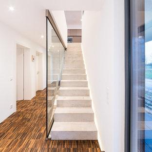 Пример оригинального дизайна: прямая лестница среднего размера в стиле модернизм с бетонными ступенями, бетонными подступенками и стеклянными перилами