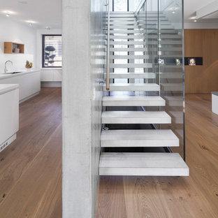 Exempel på en mellanstor modern rak betongtrappa, med öppna sättsteg och räcke i trä