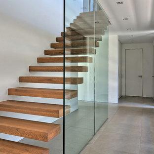 Immagine di una grande scala a rampa dritta minimalista con pedata in legno e nessuna alzata