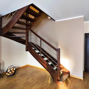 Exempel på en mycket stor klassisk svängd trappa i trä, med öppna sättsteg