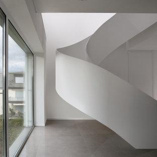 他の地域の大きい金属製のコンテンポラリースタイルのおしゃれならせん階段 (金属の蹴込み板、金属の手すり) の写真