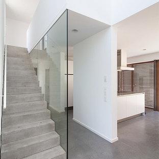 Ispirazione per una scala a rampa dritta contemporanea di medie dimensioni con pedata in cemento e alzata in cemento