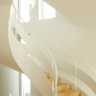 На фото: большая изогнутая лестница в современном стиле с деревянными ступенями и деревянными подступенками с