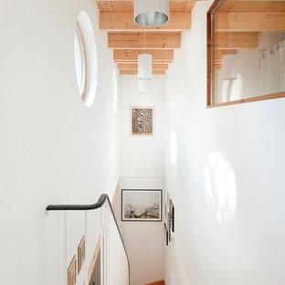 Ejemplo de escalera curva, nórdica, grande, con escalones de madera y contrahuellas de madera
