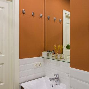 Ejemplo de aseo contemporáneo, pequeño, con baldosas y/o azulejos blancos, baldosas y/o azulejos de porcelana, armarios con paneles lisos, puertas de armario de madera en tonos medios y parades naranjas