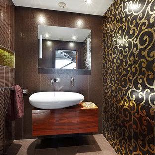 Идея дизайна: туалет в современном стиле с плоскими фасадами, фасадами цвета дерева среднего тона, коричневой плиткой, настольной раковиной и бежевым полом