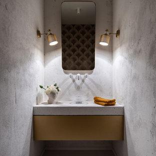 Пример оригинального дизайна: маленький туалет в современном стиле с плоскими фасадами, серыми стенами, настольной раковиной, серым полом и белой столешницей