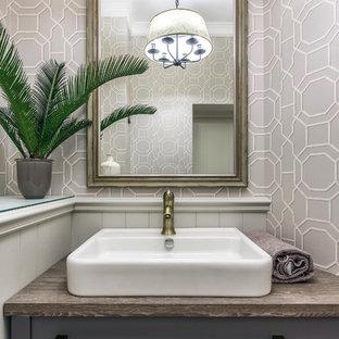 他の地域の小さいトランジショナルスタイルのおしゃれなトイレ・洗面所 (壁掛け式トイレ、磁器タイルの床、オーバーカウンターシンク、ラミネートカウンター) の写真