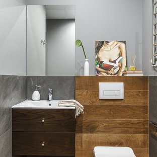 Contemporary cloakroom in Moscow with flat-panel cabinets, dark wood cabinets, a two-piece toilet, grey tiles and grey walls.