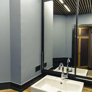 Ejemplo de aseo industrial, de tamaño medio, con sanitario de pared, baldosas y/o azulejos azules, baldosas y/o azulejos de cerámica, paredes azules, suelo de baldosas de cerámica, lavabo encastrado, encimera de madera, suelo naranja y encimeras amarillas